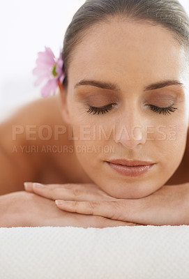 Buy stock photo Closeup of a beautiful young woman with a flower in her hair lying on her stomach