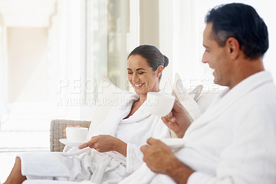 Buy stock photo Shot of a loving mature couple enjoying a drink while relaxing together at a day spa