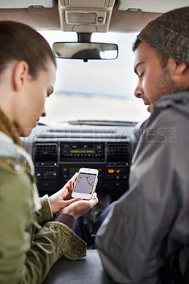 Buy stock photo Cropped shot of a young couple checking their gps while on a roadtrip.The commercial product(s) or designs displayed in this image represent simulations of a real product, and are changed or altered enough so that they are free of any copyright infringements. Our team of retouching and design specialists custom designed these elements for each photo shoot