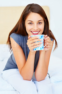 Buy stock photo Smiling young woman with coffee cup sitting on bed