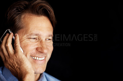 Buy stock photo Closeup portrait of a happy young male executive talking on cellphone against dark background
