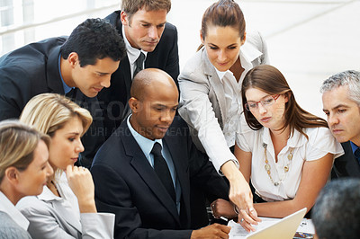 Buy stock photo Female executives viewing proposal on laptop to his colleagues