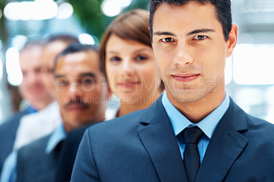 Buy stock photo Focus on businessman with executives standing behind him