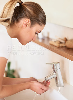Buy stock photo Cropped shot of a young woman washing her face in the bathroom