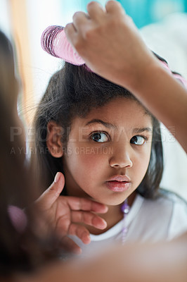 Buy stock photo Shot of a nervous little girl watching as her mother puts curlers in her hair
