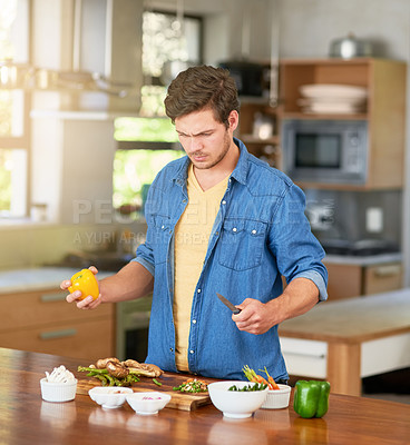 Buy stock photo Shot of a confused young man looking at recipe ingredients on a kitchen counter at home