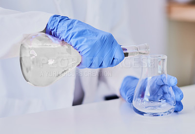 Buy stock photo Cropped shot of a scientist mixing chemicals in beakers while standing in a laboratory