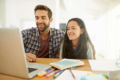 Buy stock photo Shot of a father and daughter looking at something on a laptop