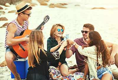 Buy stock photo Shot of a young man playing guitar for his friends while chilling on the beach