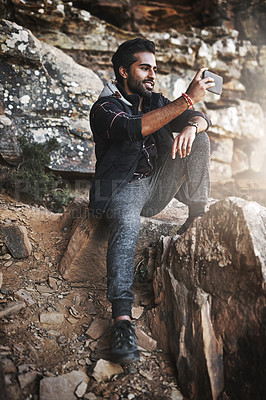 Buy stock photo Shot of a handsome young man taking photographs while hiking in the mountains