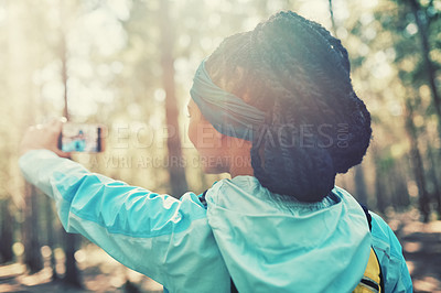 Buy stock photo Cropped shot of an athletic young woman taking selfies while jogging in the woods