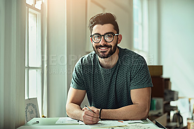 Buy stock photo Cropped portrait of a handsome young designer working on a drafting table in the office