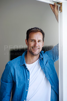 Buy stock photo Cropped portrait of a handsome man leaning against a door at home
