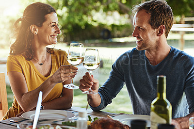 Buy stock photo Shot of a happy married couple enjoying lunch together outside