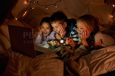 Buy stock photo Shot of three young children using a laptop in a blanket fort