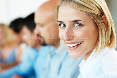 Buy stock photo Closeup of a pretty young businesswoman smiling in a meeting with her business colleagues in background