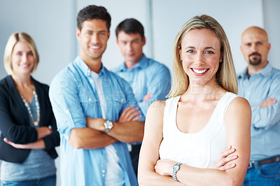 Buy stock photo Portrait of confident young female business executive with her team in the background