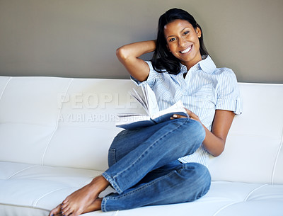 Buy stock photo View of woman curled up on sofa holding book