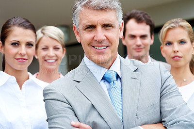 Buy stock photo Happy mature businessman smiling with his successful team in background
