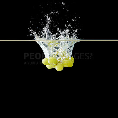 Buy stock photo Cluster of green grapes falling into water against black background