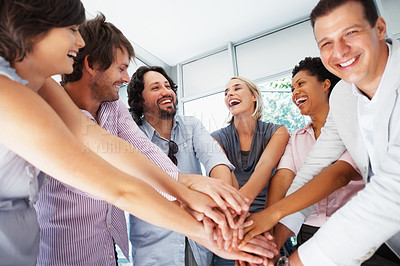 Buy stock photo Happy business people with their hands piled on each other