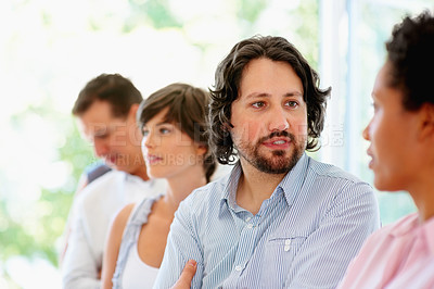 Buy stock photo Man having discussion with woman with team in background