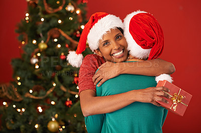 Buy stock photo Shot of a young woman embracing her friend after receiving a Christmas gift from her