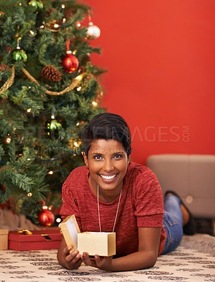Buy stock photo Shot of an attractive young woman opening her present by the Christmas tree