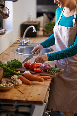 Buy stock photo Cropped shot of an attractive young woman chopping vegetables in the kitchen