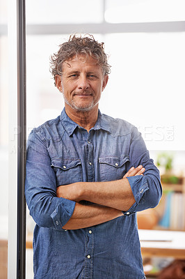 Buy stock photo Portrait of a mature businessman standing with his arms folded in an office