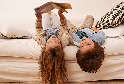 Buy stock photo Shot of two young children lying on their backs and reading a book together