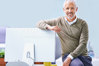 Buy stock photo Portrait of a mature businessman in his office leaning on his computer monitor