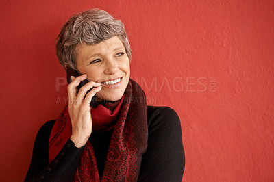 Buy stock photo Shot of a beautiful senior woman talking on her mobile phone in front of a red background