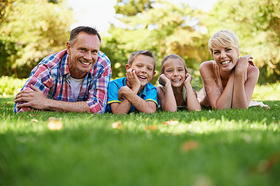 Buy stock photo A front view portrait of a happy family lying on the grass outdoors