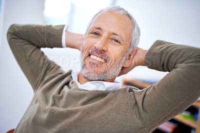 Buy stock photo A cropped portrait of a relaxed and carefree businessman sitting at his desk