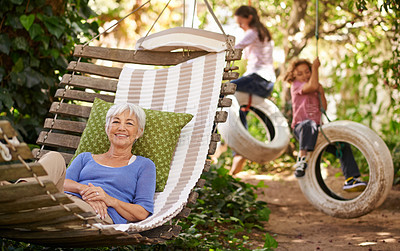 Buy stock photo Portrait of a senior woman lying in a hammock out in the garden while her grandchildren play in the background