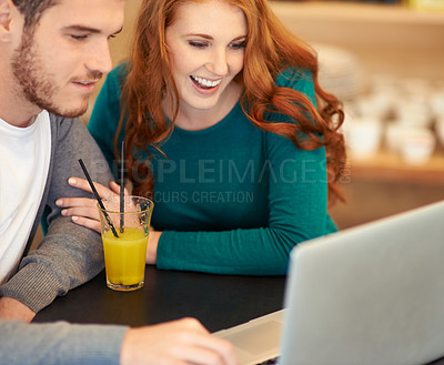 Buy stock photo Shot of a young couple using a laptop while having a drink at a cafe