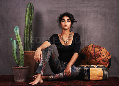 Buy stock photo Studio portrait of a beautiful young woman sitting amongst cacti and cushions