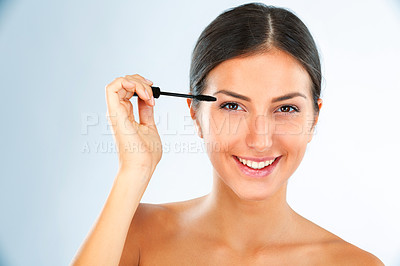 Buy stock photo Studio portrait of an attractive young woman applying mascara to her eyelashes