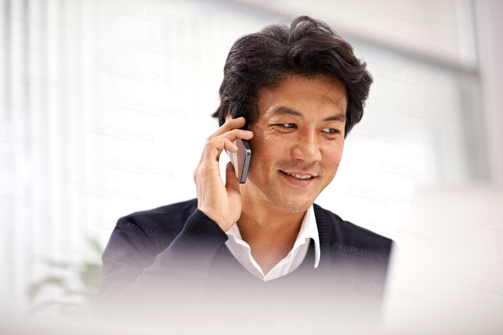 Buy stock photo Shot of a handsome asian businessman on the phone while working at his desk