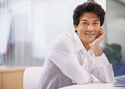Buy stock photo Portrait of a handsome asian businessman sitting at his office desk