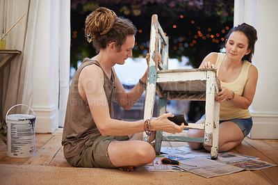 Buy stock photo A young woman sanding down an antique chair