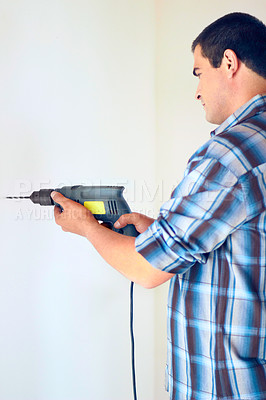 Buy stock photo Shot of an attractive man drilling into a wall