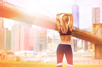 Buy stock photo Rear view shot of a beautiful woman stretching  before her run with the city in the background