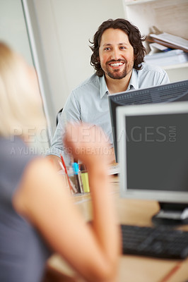 Buy stock photo Handsome business man discussing with colleague in the office