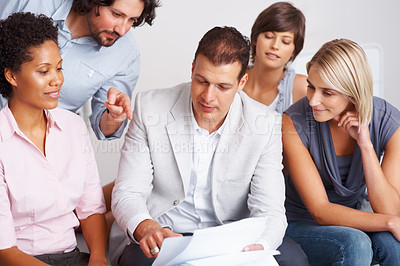 Buy stock photo Young business man pointing towards the paperwork with his team