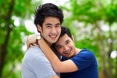 Buy stock photo Portrait of an affectionate young gay couple spending time together outdoors