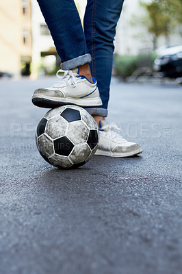 Buy stock photo Cropped image of a man's foot on a soccer ball in the street