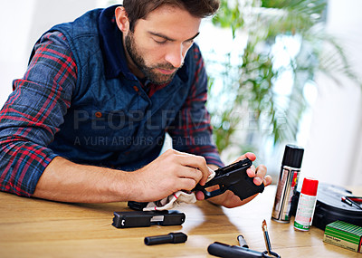 Buy stock photo A young man cleaning his gun