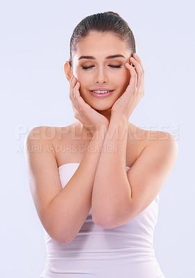 Buy stock photo Studio shot of a beautiful young woman touching her flawless skin